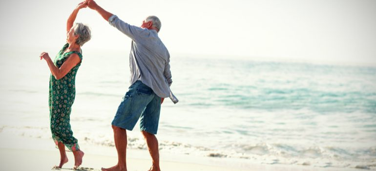 Retired couple dancing on a beach